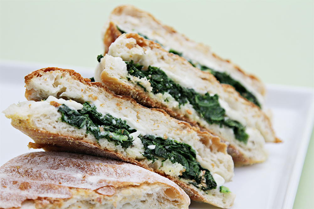 Buffalo mozzarella and spicy kale panini on ciabatta rolls